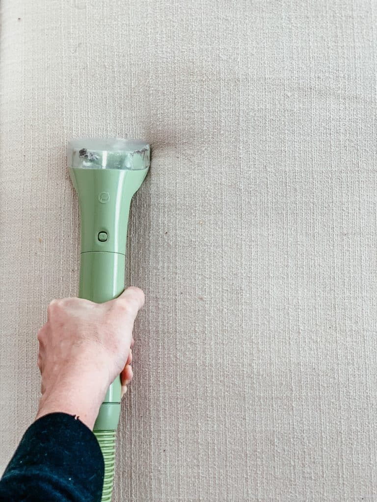 this is a photo of a steam cleaner wand being used on white fabric
