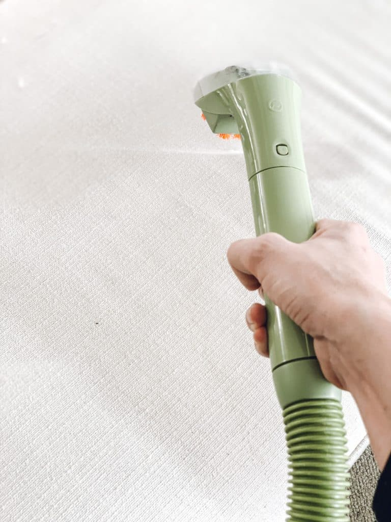 this is a photo of a steam cleaner wand spraying water on white fabric