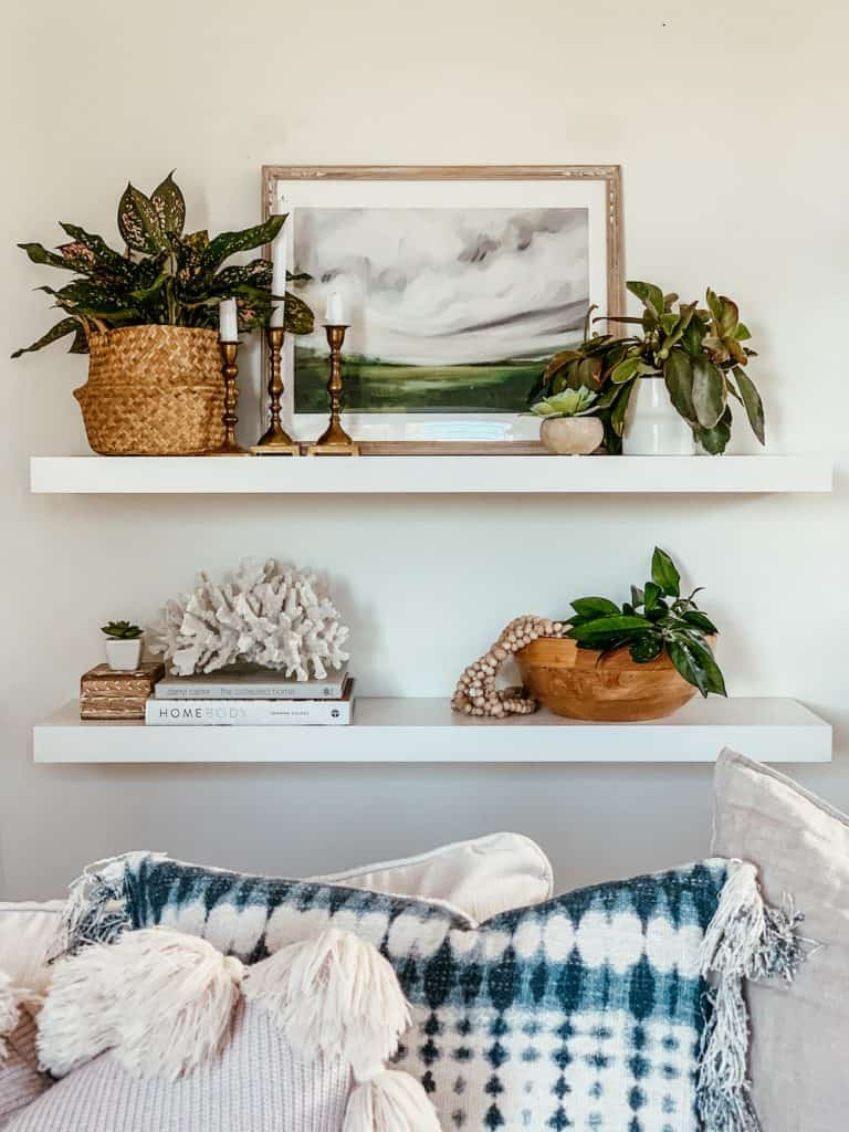 this is a photo of two floating shelves decorated with an easy shelf styling method