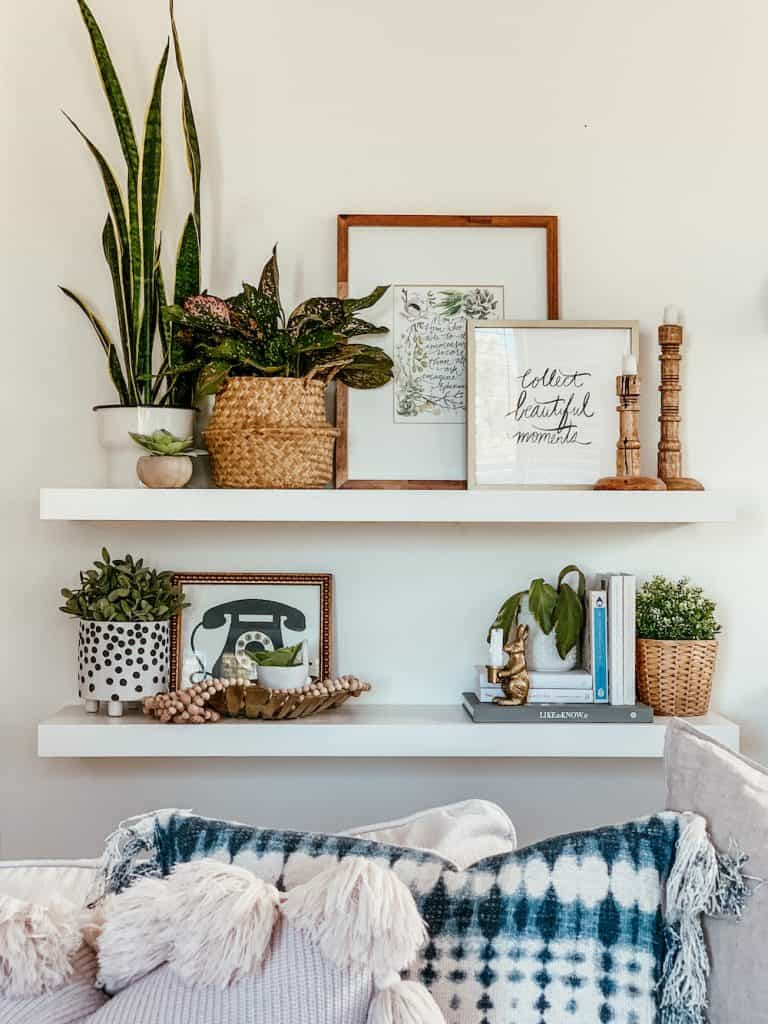 this is a photo of two floating shelves with plants and pictures on them and pillows on a sectional