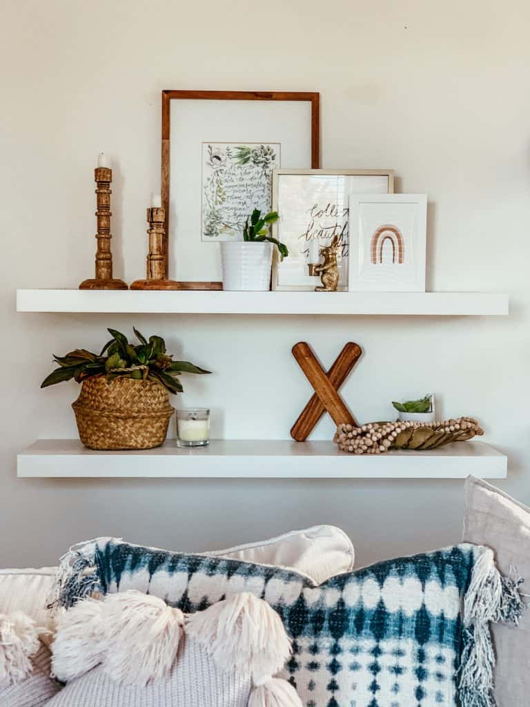 this is a photo of two floating shelves with home decor on them