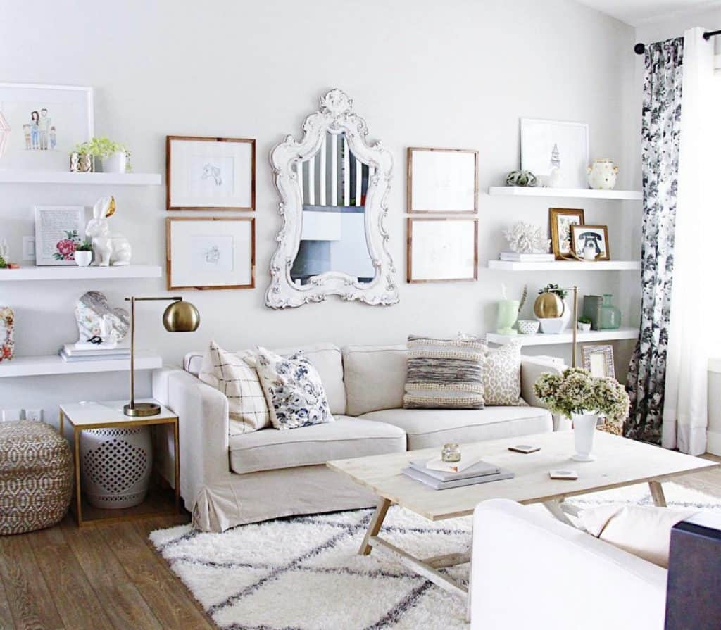 this is a photo of a white living room with a cream couch and a large white mirror with floating shelves