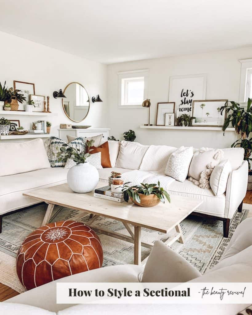 living room with cream sectional, leather pouf, lots of plants and home decor