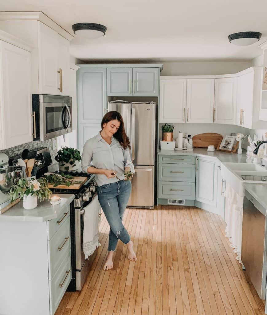 this is a women standing in a small kitchen thats been renovated for cheap