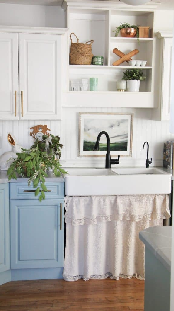 this is a photo of a farmhouse sink and ruffle curtain in a renovated small farmhouse style kitchen