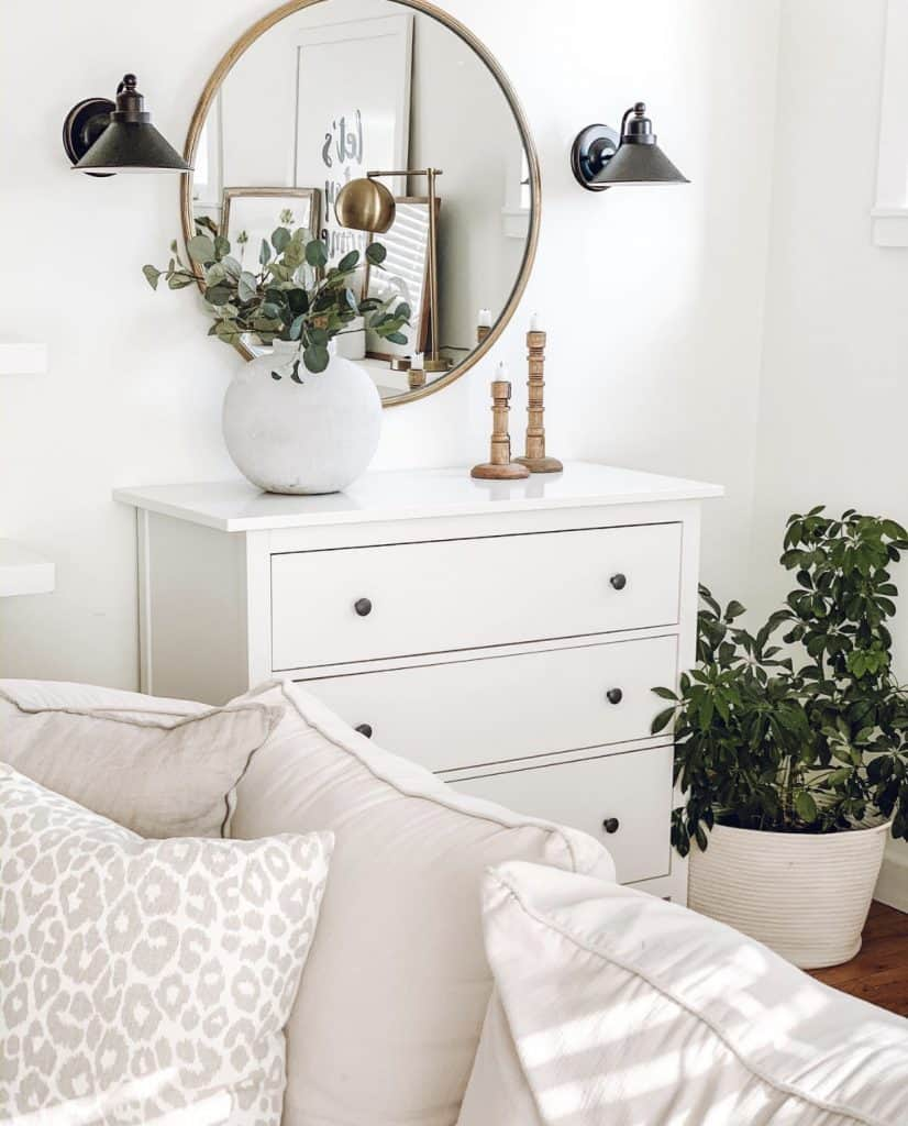 white dresser with gold round mirror and black wall sconces
