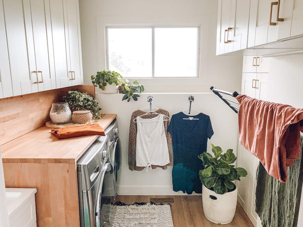 small modern farmhouse laundry room with wooden countertop and drying racks