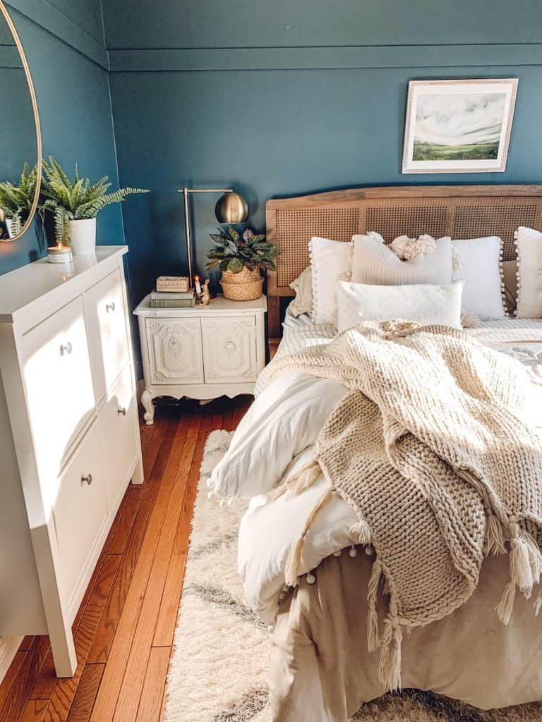master bedroom with blue walls and cane headboard