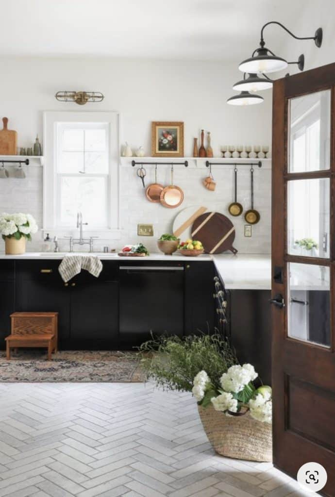farmhouse kitchen with tiled floors, black lower cabinets and peg rail shelves