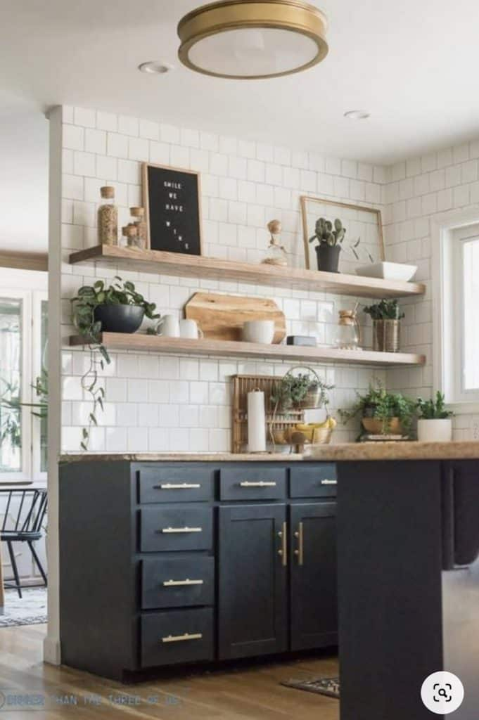 dark grey cabinets with floating open shelves and white square subway tile