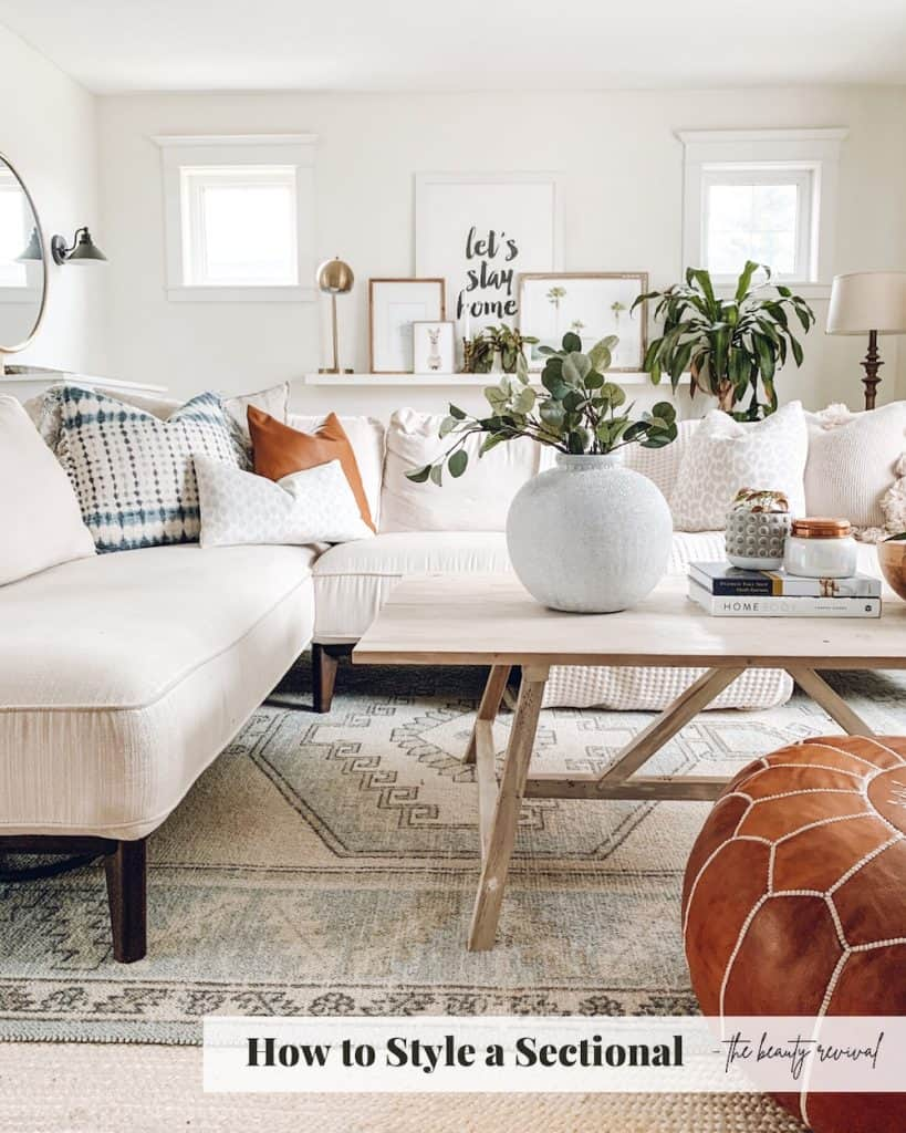 living room with a white sectional, wood coffee table, leather pouf and assortment of pillows