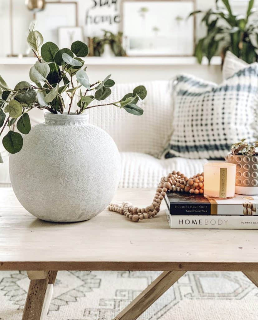 living room coffee table with large white vase and faux eucalyptus stems