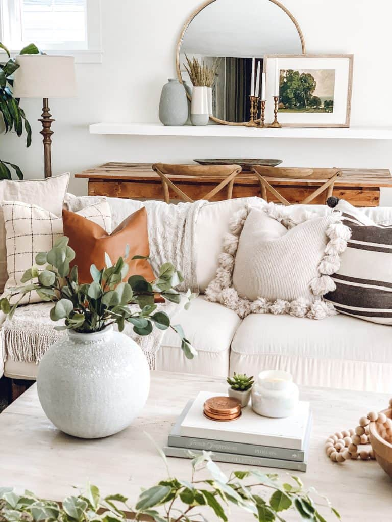 boho farmhouse living room featuring a hand painted vase, throw pillows, rustic decor