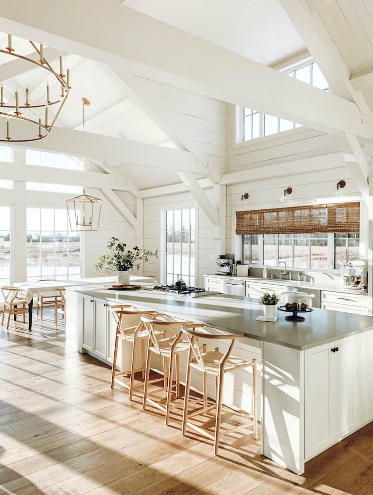 this is a photo of a white shiplap walled kitchen with vaulted ceilings and a large island surrounded by wishbone stools