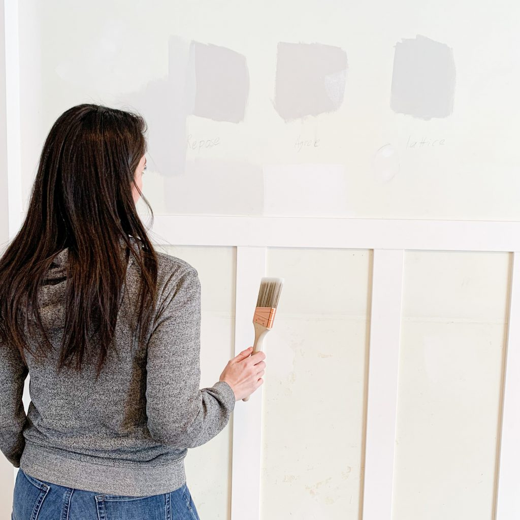 this is a photo of a woman painting paint samples on a wall