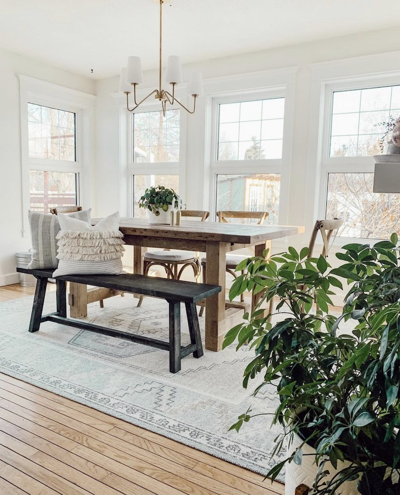 this is a photo of a modern farmhouse dining room with a farmhouse table and black seating bench