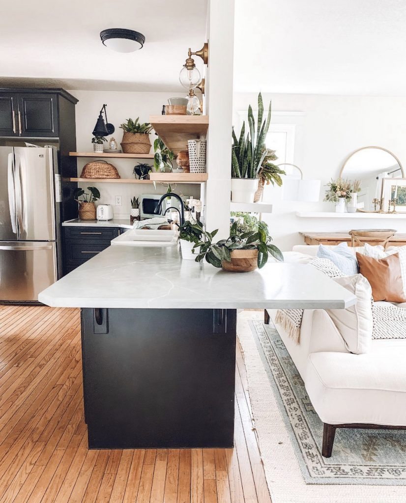 this is a photo of a black modern farmhouse kitchen and a portion of a living room