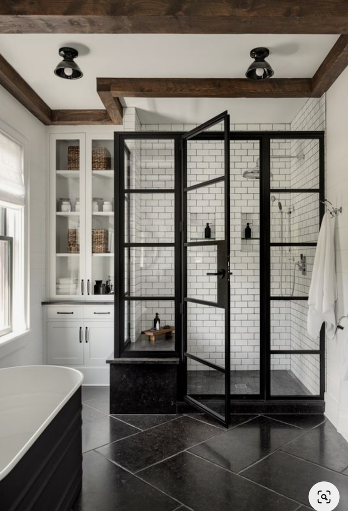 this is a photo of a modern farmhouse bathroom with wood beams and grid bathroom shower door