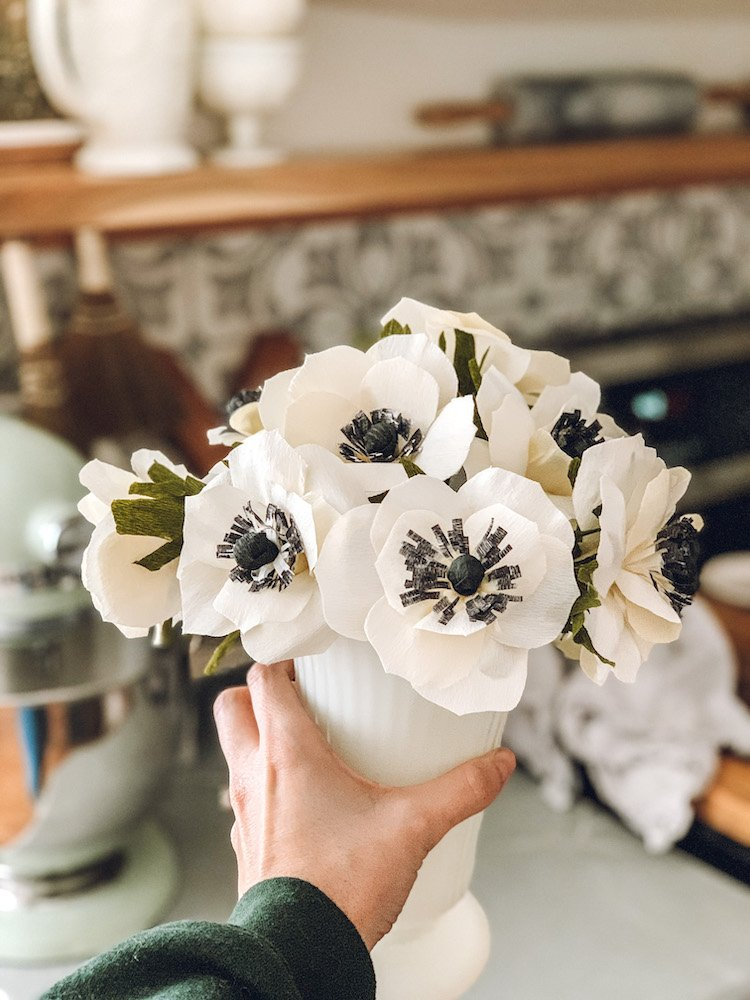 this is a photo of a hand holding crepe paper anemones in a white vase