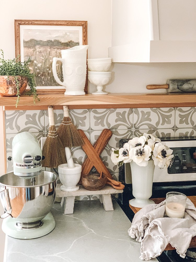 this is a photo of a kitchen counter with a mixer, a little stool with salt and pepper and a bouquet of crepe paper flowers