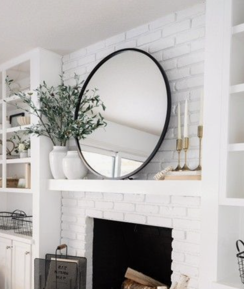 this is a photo of a brick fireplace with a large black round mirror