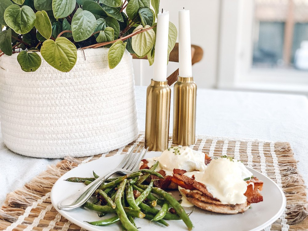 this is a photo of Eggs Benedict and green beans on table