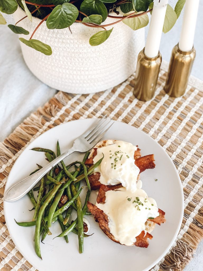 this is a photo of Eggs Benedict with hollandaise sauce, fresh green beans salted in olive oil and garlic on a woven placemat