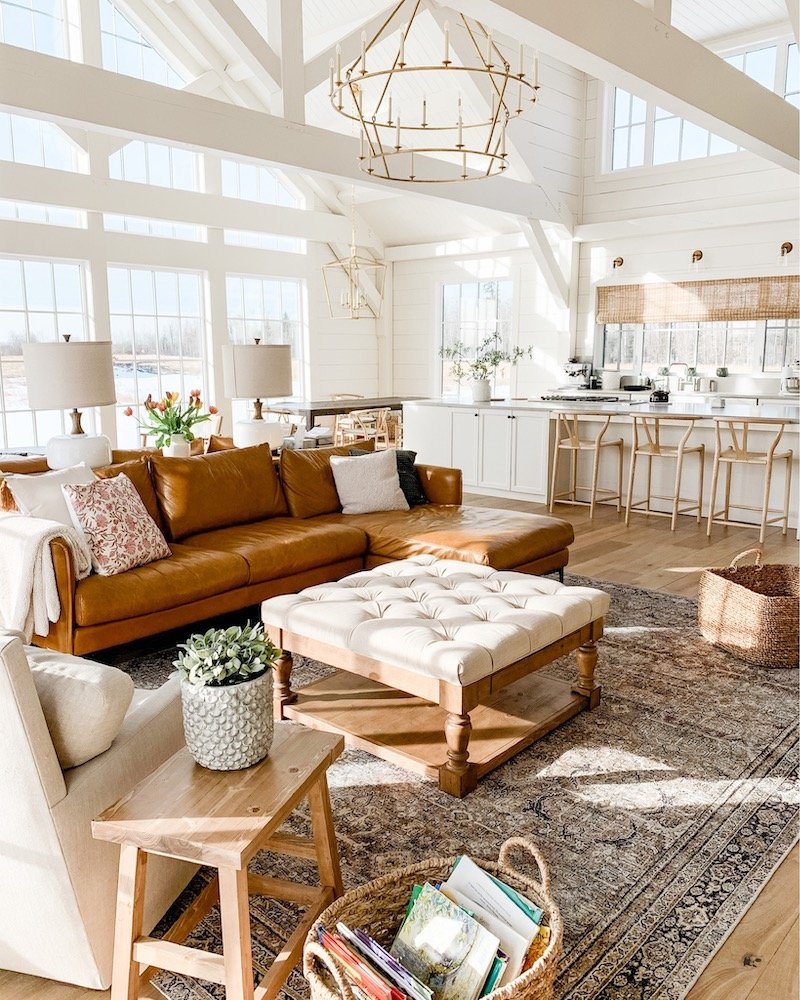this is a photo of a modern farmhouse living room with a tan leather sectional, loll rug, tufted ottoman and large gold candle chandelier