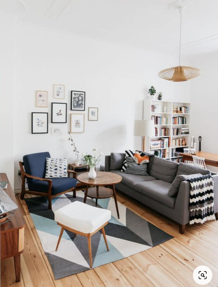 this is a photo of a living room with a rug that is too small