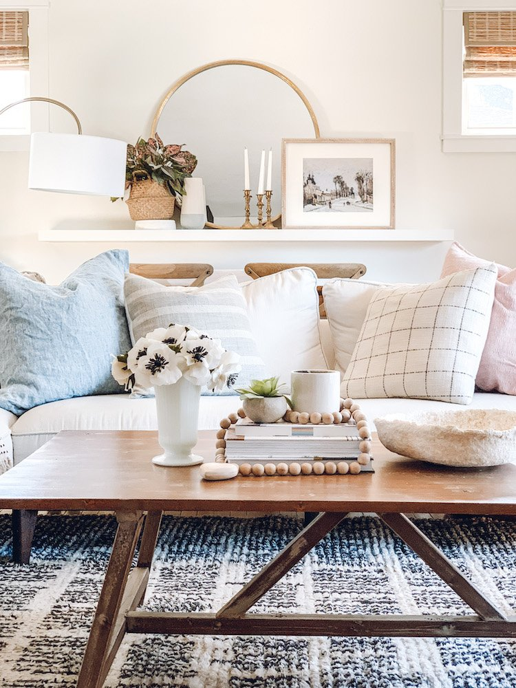 this is a photo of a rustic coffee table with spring decor ideas. A vase full of anemones and a stack of books and decor on it