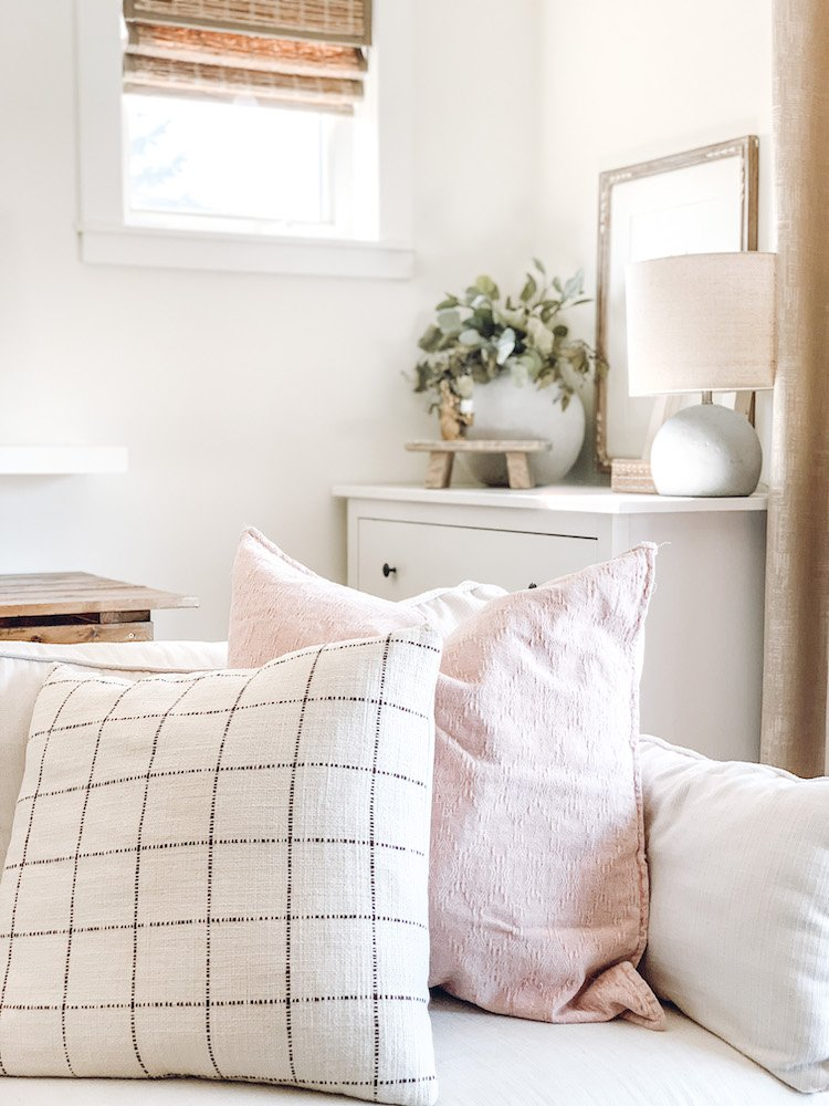 this is a photo of  two pillows on a sectional and a dresser in the back ground with home decor on it