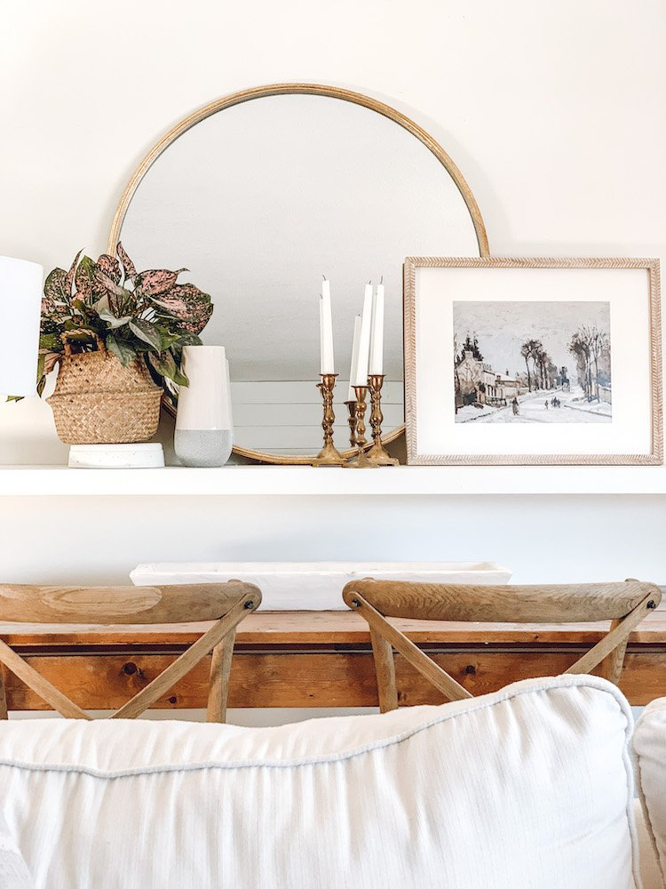 this is a photo of a of a large floating shelf with spring decor ideas. A gold round mirror and a white dough bowl on a craft table