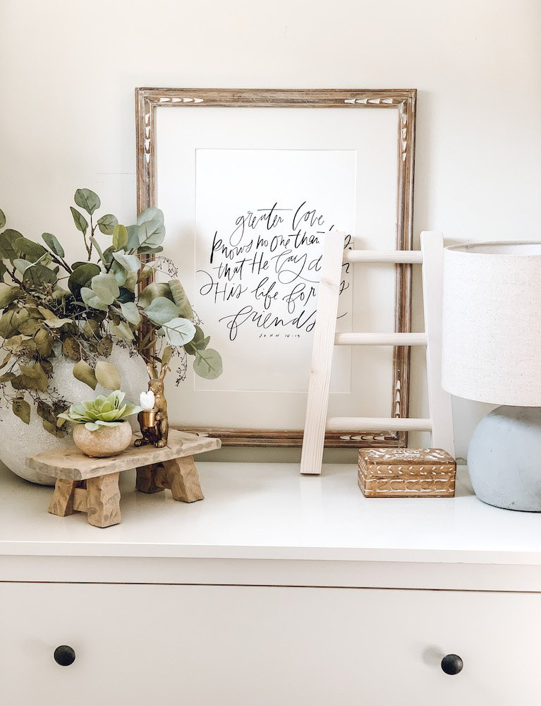 this is a photo of a dresser decorated for spring with wooden objects and greenery. A brass bunny sits on a display stool