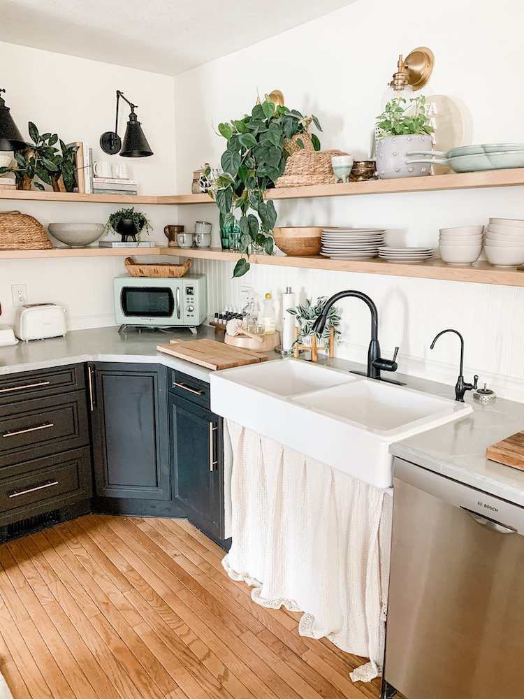 this is a photo of a black kitchen with open shelves and a farmhouse sink