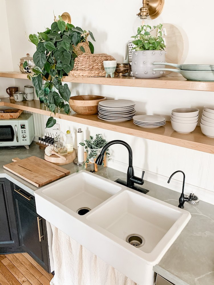 this is a photo of a kitchen with open shelves and an ikea haves apron front double bowl sink