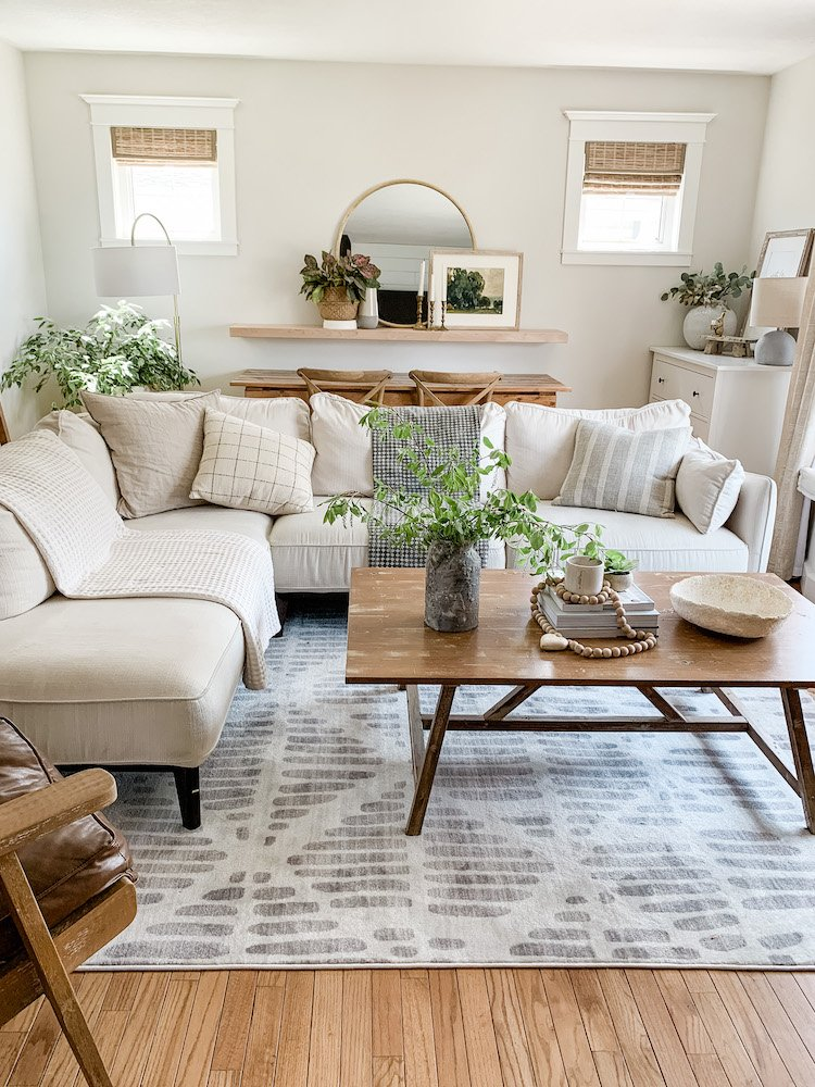 this is a photo of a neutral living room with a white and grey geometric rug, rustic coffee table, large white sectional