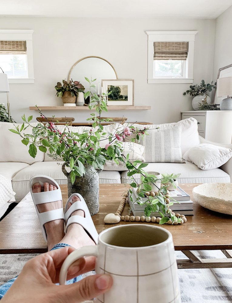 this is a photo of a lady drinking a cup of coffee in a modern farmhouse living room