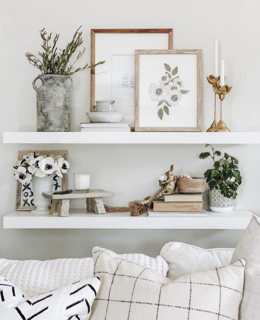 this is a photo of white floating shelves, boho home decor, brass candlesticks, vintage cooks, anemone flowers, pillows