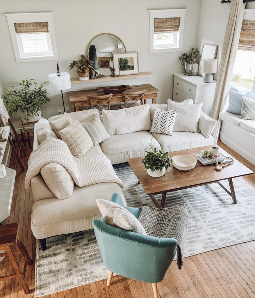 this is a photo of a mid century boho living room with wood tones and a large white sectional