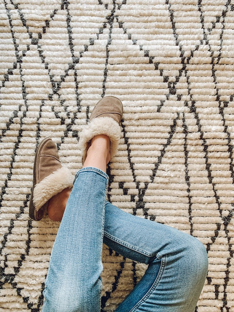 this is a photo of a woman sitting on a shag boho rug