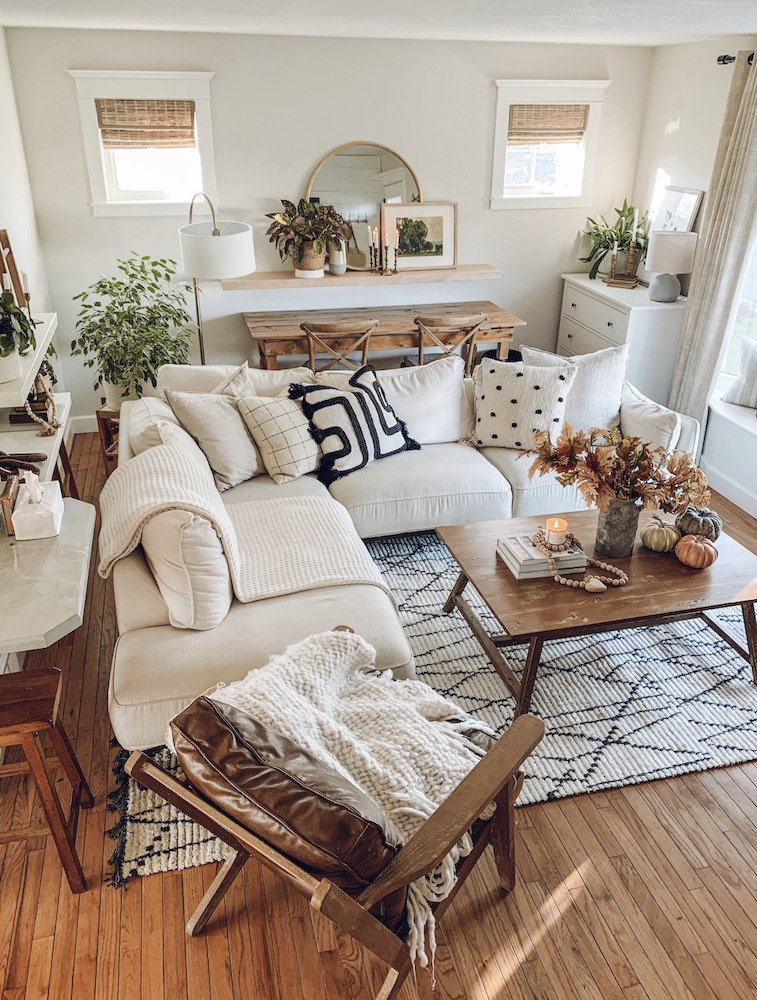 this is a photo of a boho mid century modern living room with white sectional, bamboo blinds, and boho rug