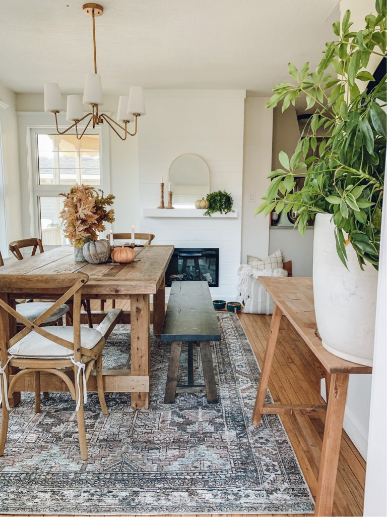 this is a photo of a small dining room with the Billie clay/sage amberlewis x loloi rug under a farmhouse dining table