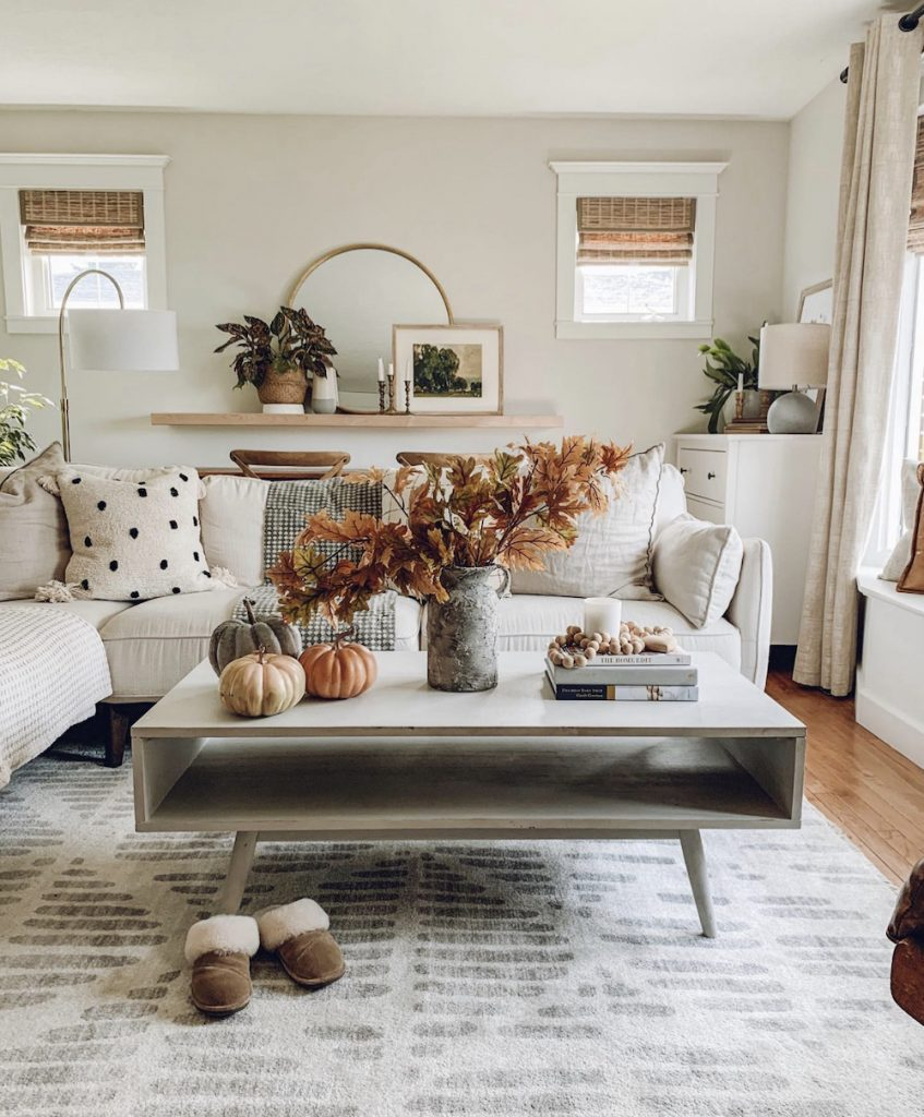 this is a photo of a mid century grey coffee table with faux fall branches in a modern farmhouse living room