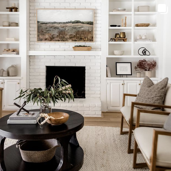 this is a photo of a modern farmhouse living room with black modern coffee table, mid century side chairs and white brick fireplace with white mantel