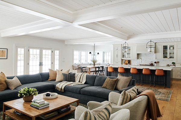this is a photo of a living room with a large blue sectional, looking into a modern farmhouse kitchen with leather bar stools