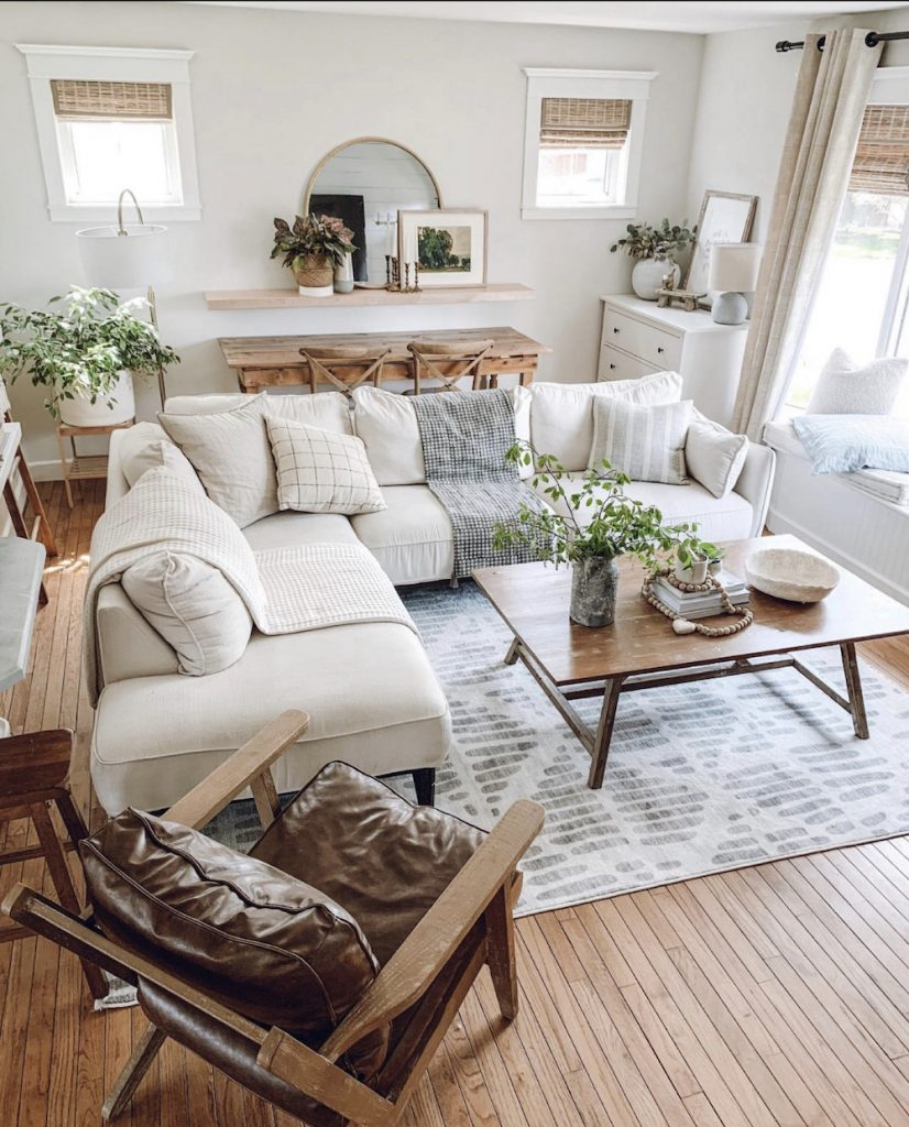 this is a photo of a modern farmhouse living room with a light white sectional and grey and white rug