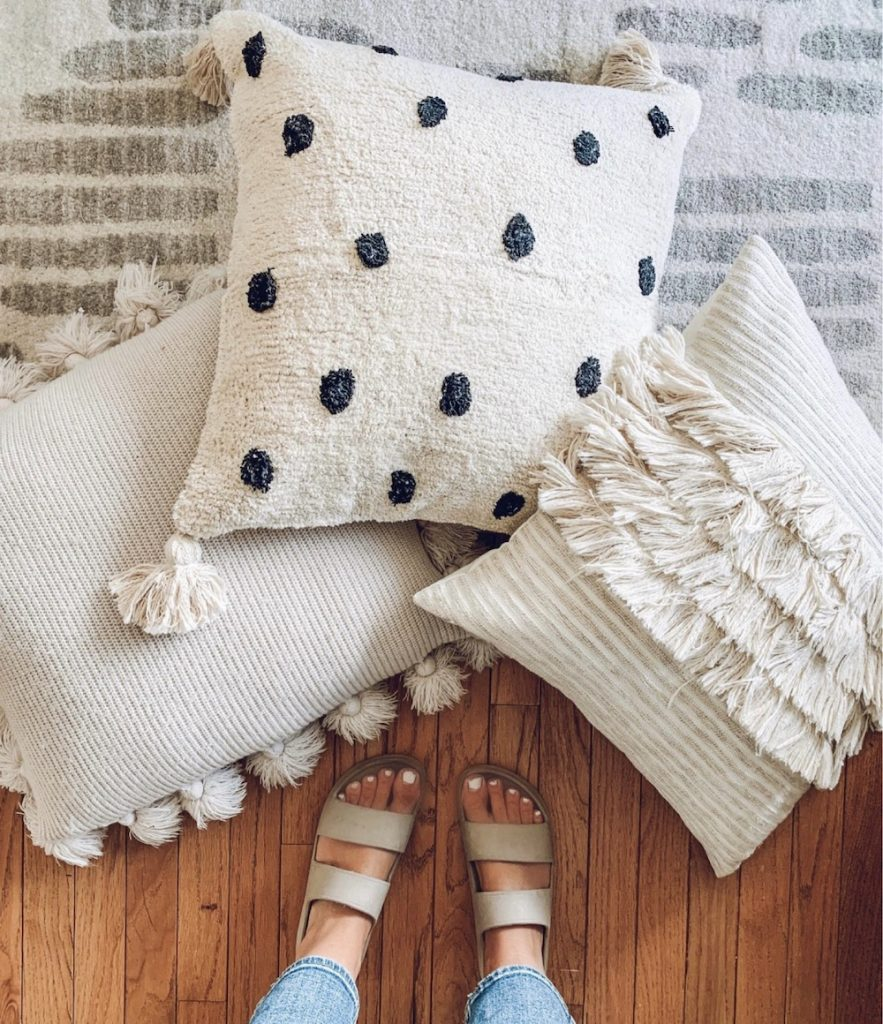 this is a photo of three boho textured pillows on a floor with a woman standing over them