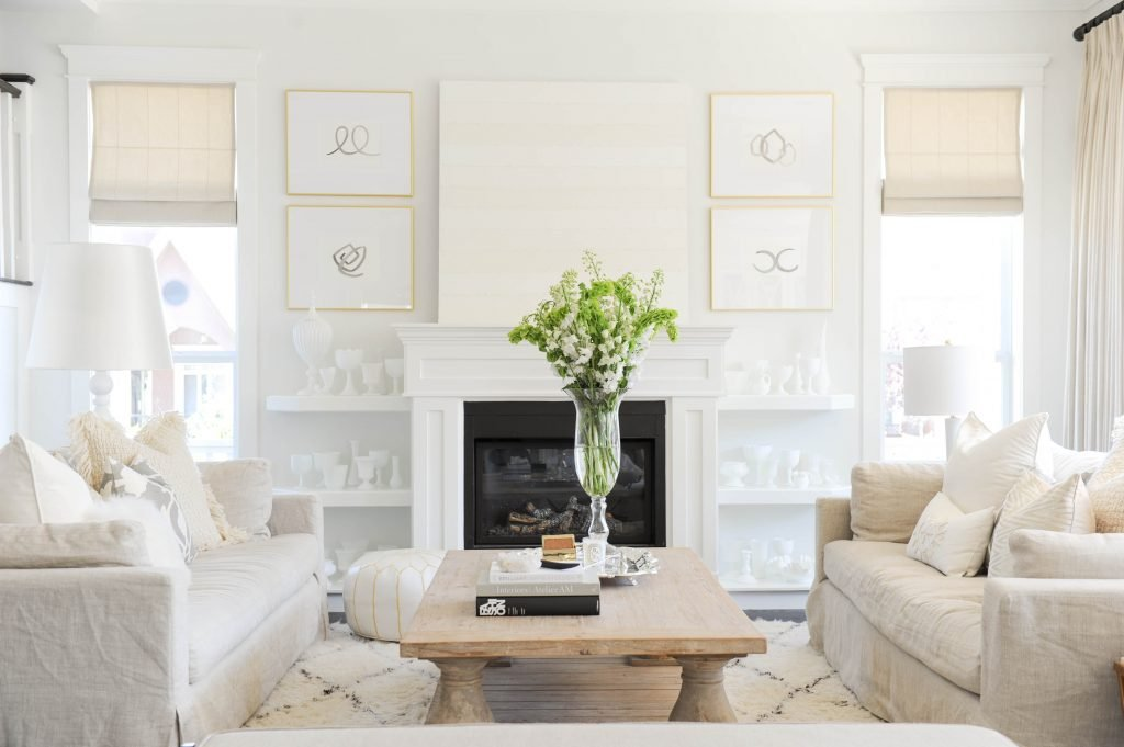 this is a photo of a light, white living room with rustic coffee table and vase of tall flowers