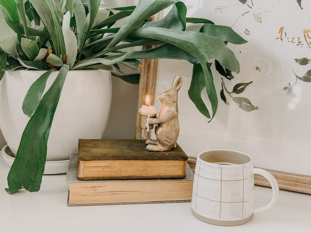 this is a photo of a bunny candle on some vintage books and a mug of coffee